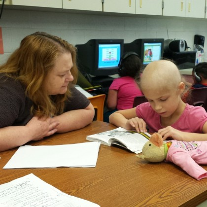 Chloe reading with her teacher while home on the last break between rounds of chemo.